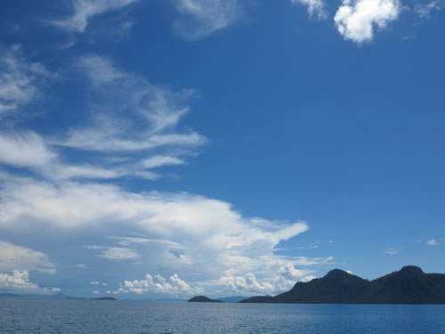 Royalty free image - Tropical blue sea with land and white clouds