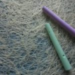 Two sticks of chalk, one green one purple
